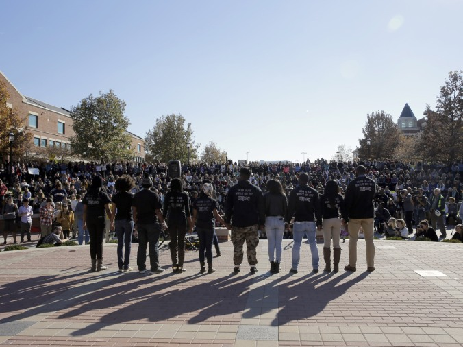 Members of the student protest group Concerned Student 1950 hold hands following the announcement that University of Missouri System President Tim Wolfe would resign.